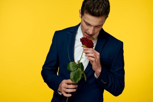 彼の手にバラとセクシーな表情のクラシックなスーツの若い男