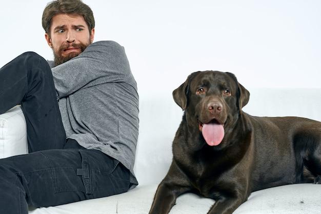 Счастливый человек на диване со своей собакой, изоляции и карантина с собакой дома