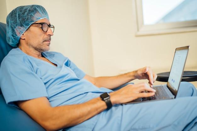 手術後のラップトップを使用して医師の外科医