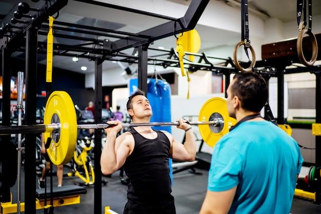 Двое мужчин, обучение в тренажерном зале, поднятие тяжестей.