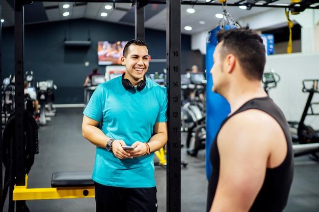 Двое мужчин тренируются в тренажерном зале, глядя на мобильный телефон