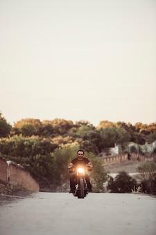 Водитель управляет своим мотоциклом на закате