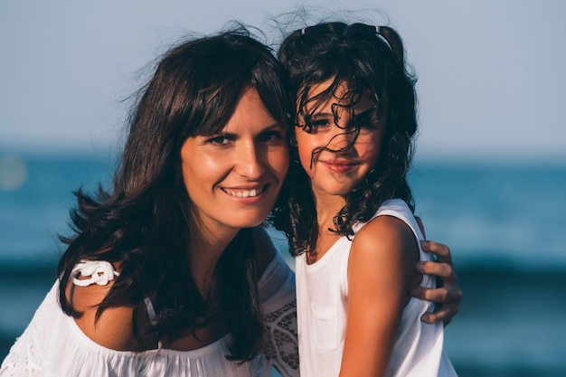 母と娘は、夕暮れ時のビーチでカメラを見てポーズします。