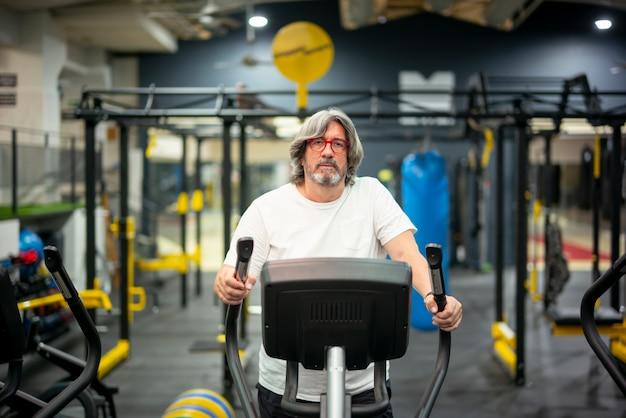 Старший взрослый человек, занятия спортом в тренажерном зале.