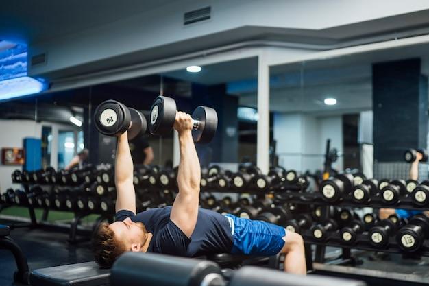 ハンサムな男がジムでボディービルの重みを練習