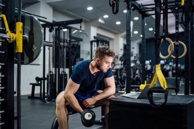 ハンサムな男のジムでボディービルの重量を練習し、ラップトップ上のメディアを見て