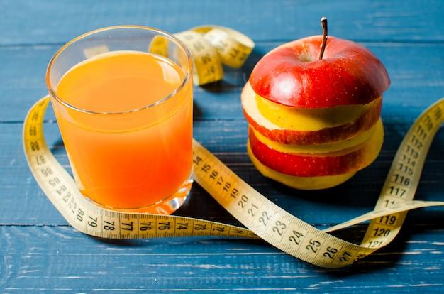Здоровый образ жизни. яблочно-апельсиновый сок на деревянном
