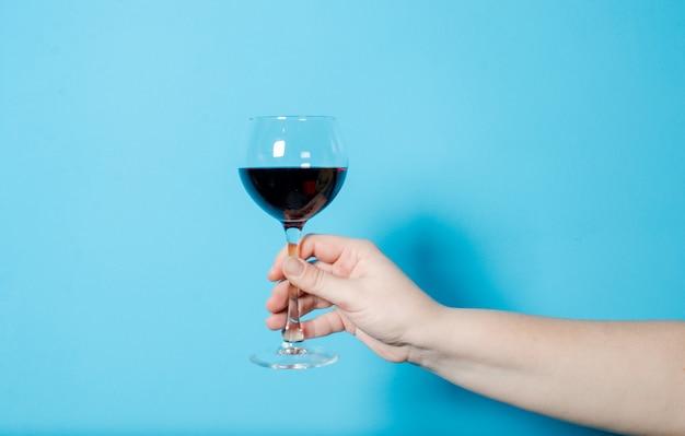 女性の手に一杯のワイン。アルコールパーティ。