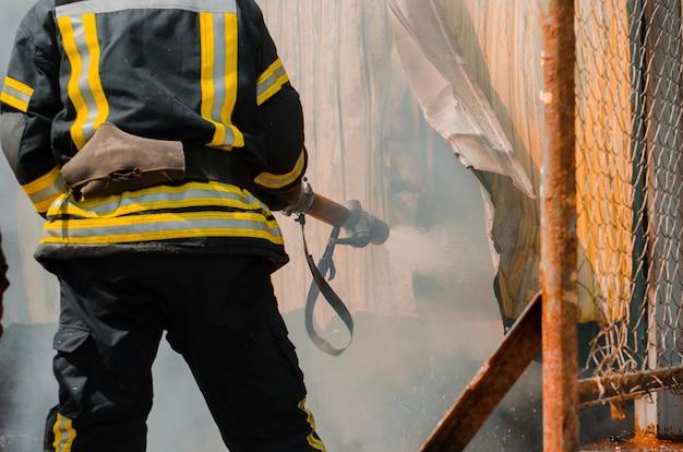 Пожарный тушит пожар. концепция спасения людей при пожаре