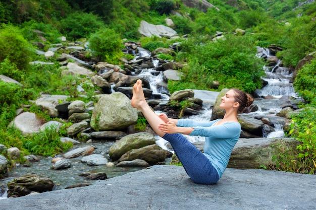 Женщина делает аштанга виньяса йога асана навасана на открытом воздухе