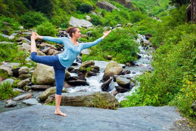 Женщина делает асаны йоги на открытом воздухе у водопада
