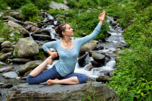 Женщина делает асаны йоги на тропический водопад