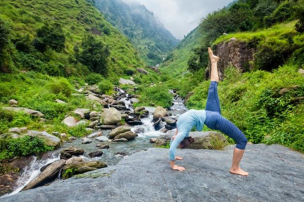 Женщина делает асаны йоги на водопад