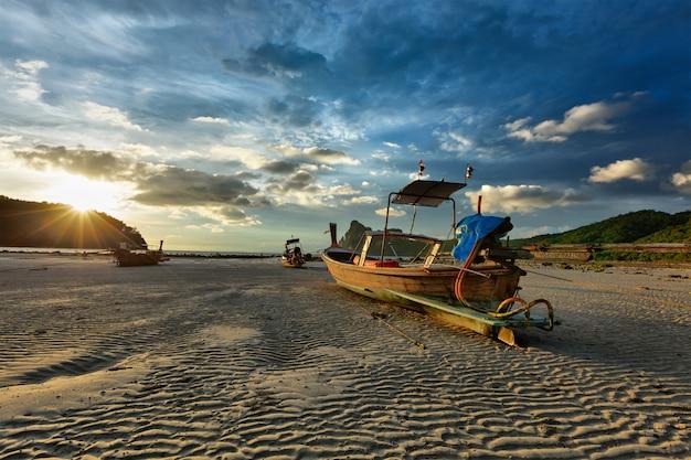 夕日のビーチでロングテールボート