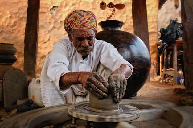 Индийский поттер на работе. ремесло ручной работы из шилпаграма, удайпура, раджастхана, индии
