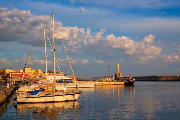 Яхты лодки в живописном старом порту ханья является одним из ориентиров и туристических направлений острова крит по утрам. ханья, крит, греция