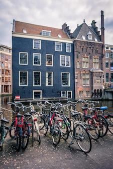古い家と運河の近くのアムステルダムの通りの自転車