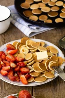 トレンディな小さなパンケーキと木製の背景にイチゴの朝食