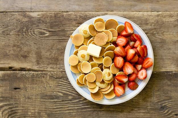 素朴な背景にイチゴとパンケーキシリアルのプレート。テキストのためのスペース