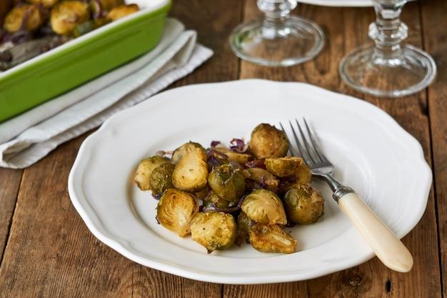 Запеченная брюссельская капуста с красным луком на белой тарелке