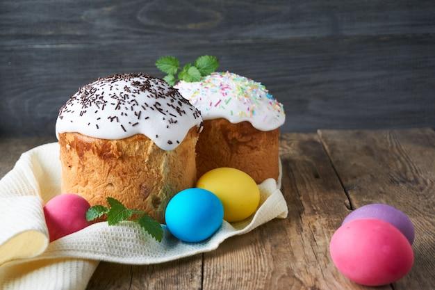 Пасхальные куличи с разноцветными крашеными яйцами на деревянном столе