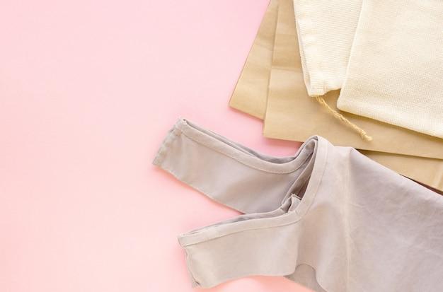 Различные типы многоразовых сумок на розовом фоне