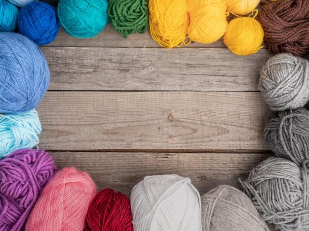 Цветная шерсть для вязания на деревянной поверхности. вид сверху. копировать пространство