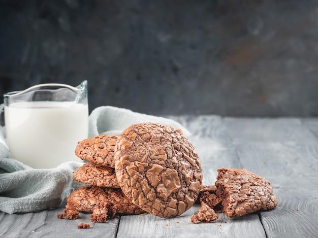 牛乳と木製のテーブルの上のブラウニークッキー。コピースペース。