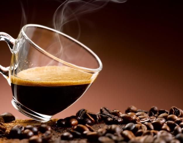 Кофе эспрессо наливается в стеклянную чашку