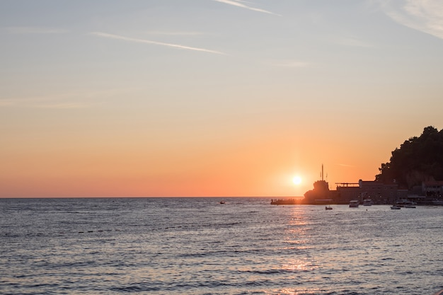 Берег моря во время заката. темная поверхность моря с отражением солнца