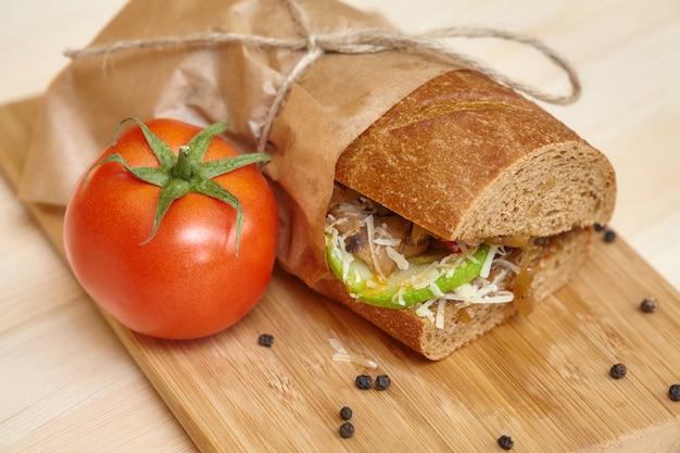 食材を使った木製のまな板に大きなサンドイッチ