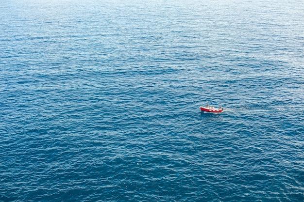 Лодка на синее море поверхности птичьего полета.