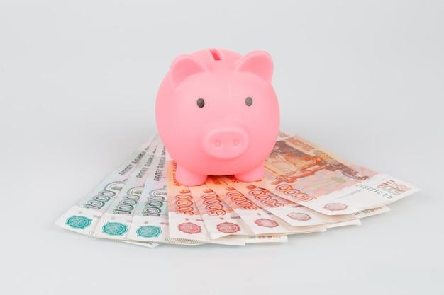 Розовая копилка на куче рублевых банкнот