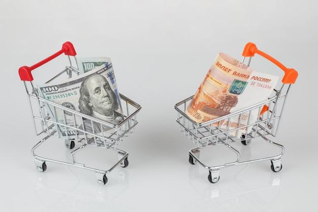 Мини-тележки с банкнотами доллара и рубля, концепция денег