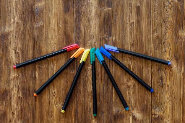 Множество разных маркерных ручек на деревянном столе