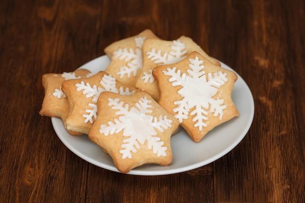 Вкусное рождественское печенье, украшенное сахаром на тарелке, крупным планом