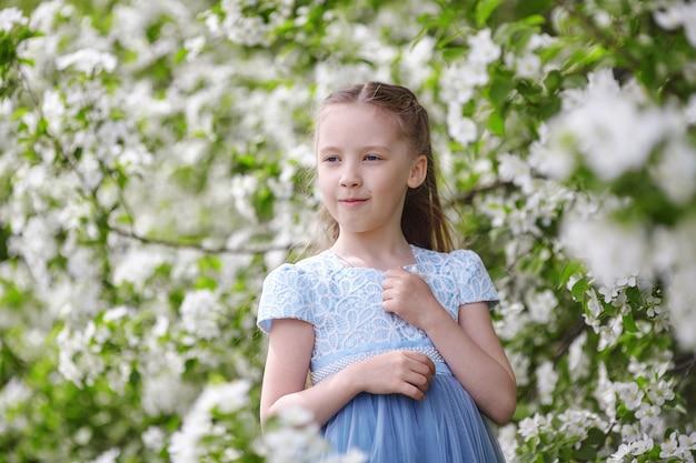 Милая маленькая девочка в цветущем саду яблонь на весну