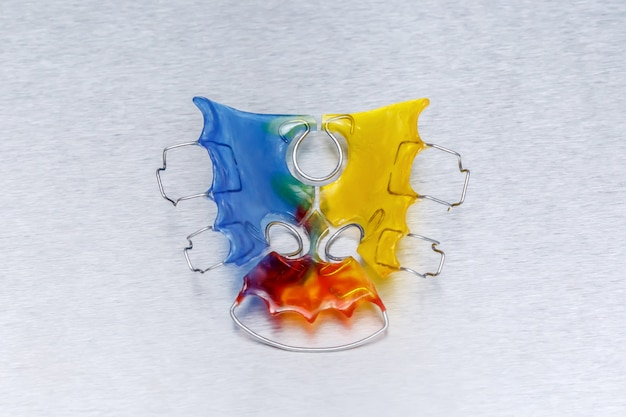 Цветные брекеты или фиксатор для зубов на металлической стене