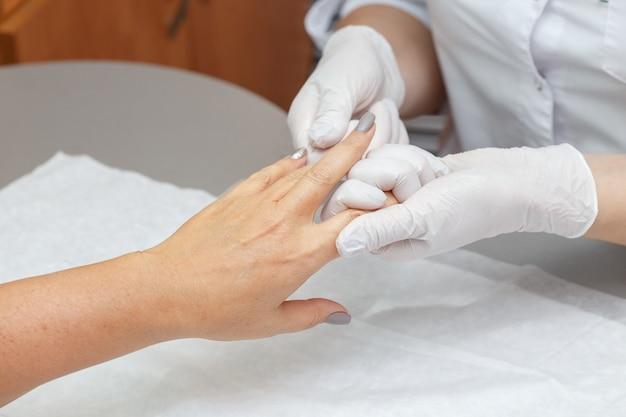 Массажист массируя руки женщины в салоне красоты