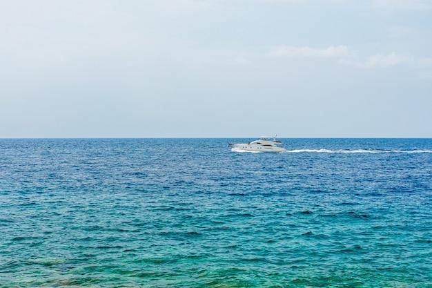 Лодка с туристами на поверхности синего моря