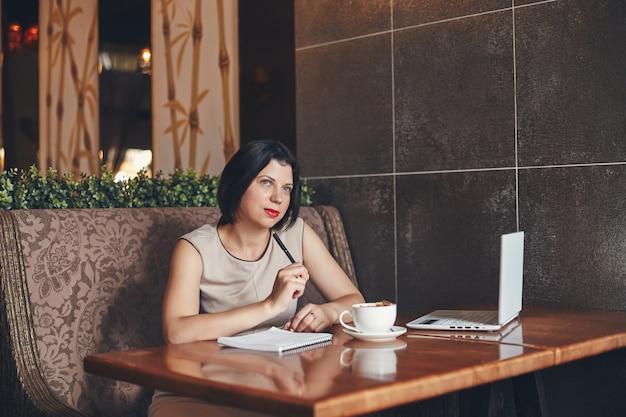 ノートパソコンとノートブックと若い白人実業家。カフェの女性