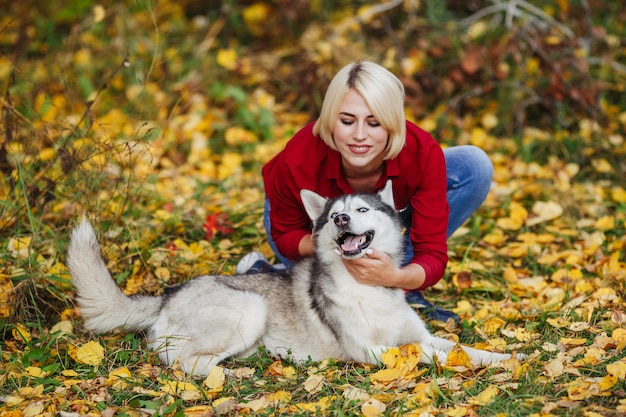 秋の森でハスキー犬と遊ぶ美しい白人少女