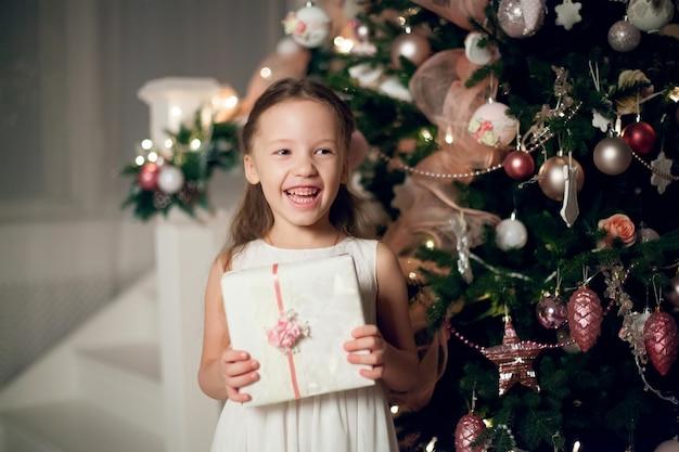 Девушка в платье, держа подарки возле елки.