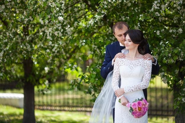 若い新婚新郎と新婦の咲く庭でピンクのウェディングブーケ
