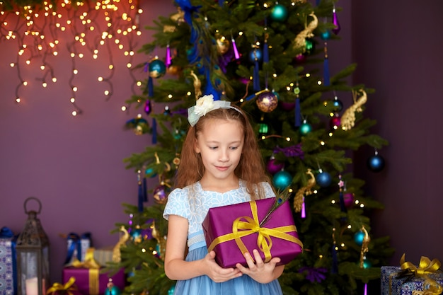 Милая девушка с длинными волосами держит подарочную коробку возле елки