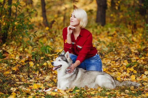 Красивая кавказская девушка играет с хаски в осеннем лесу или парке