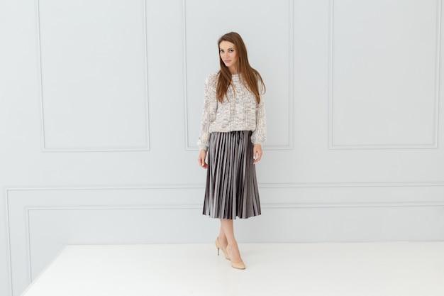ライトスタジオのスカートの女性のファッションの肖像画