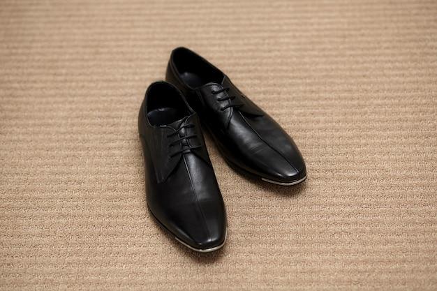 Современные черные глянцевые мужские туфли с шнурками на светлой поверхности