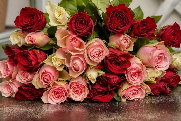 Большой букет из разноцветных роз, на столе