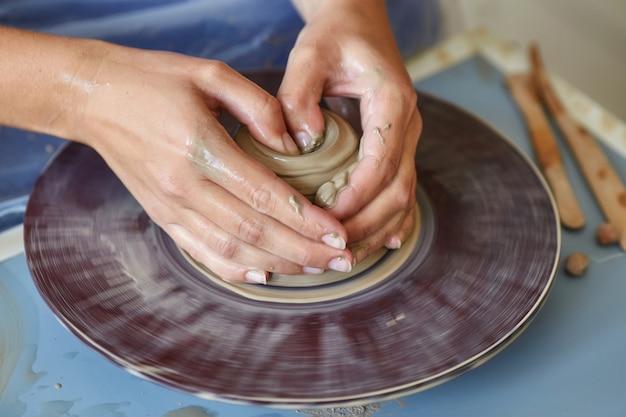 Создание банки или вазы из глины. женские руки, гончарный круг